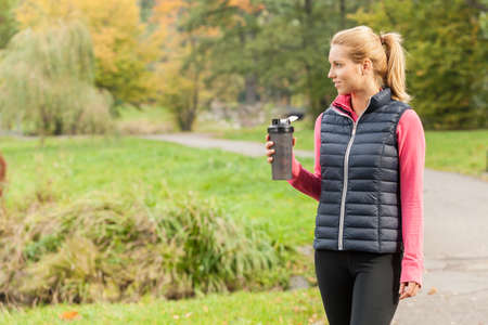 Photo of young woman drinking from water bottle after jogging photo
