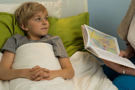 child in bed: Boy lying in bed and hearing book
