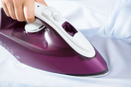 helpers: Horizontal view of close-up of ironing shirt