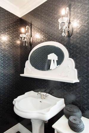 Picture of white porcelain basin with small mirror above photo