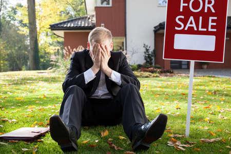 Resigned real estate broker sitting on the grass