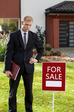 selling house: Realtor standing in front of house for sale Stock Photo
