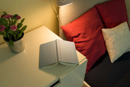 night table: Cozy bedroom interior with book lying on bedside table Stock Photo