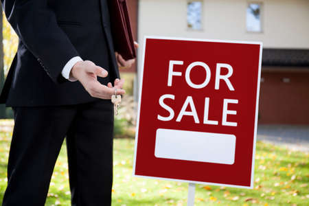 Real estate agent holding keys to home for sale