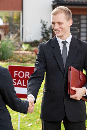 Lächelnd Immobilienmakler schütteln Hand von Kunden