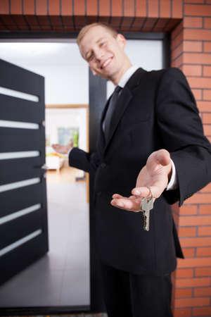 Lachend makelaar houden sleutels om schoonheid thuis Stockfoto