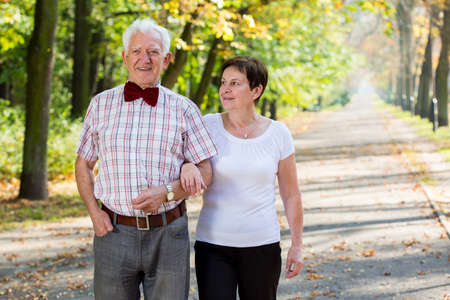 old people walking: Aged cheerful marriage and autumn stroll in park Stock Photo