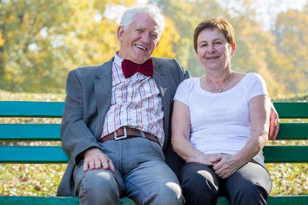 matrimonio feliz: Feliz matrimonio mayor que se sienta en un banco del parque en la tarde soleada