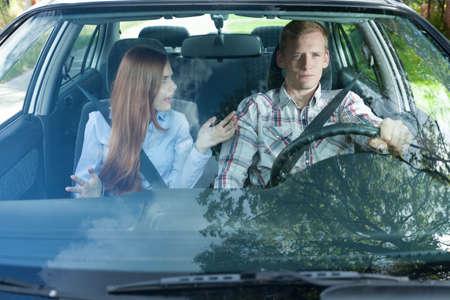 Jeune homme et la femme ayant un combat dans la voiture Banque d'images