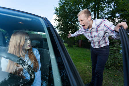 Young man screaming at a woman in car
