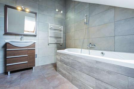 Bathroom interior with bath and wooden shelf Foto de archivo