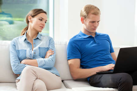 secretly: A man using a laptop and a womand secretly looking Stock Photo