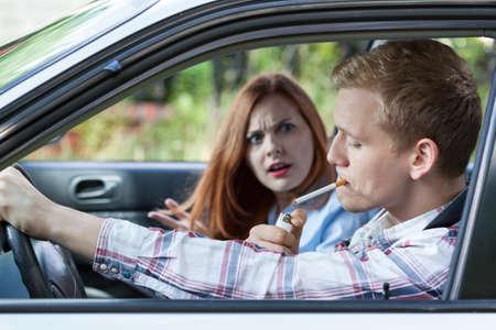 chica fumando: Mujer enojada con el hombre por fumar cigarrillos en el coche Foto de archivo