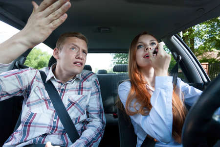 putting in: Young man mad at woman for putting on lipstick in car