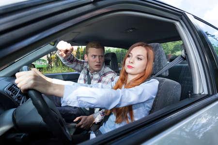 Young man angry at woman driving car