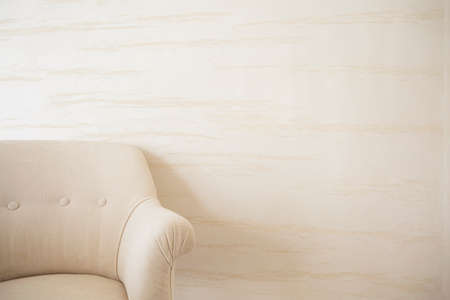 sitting room: Beige armchair on a background of bright wall