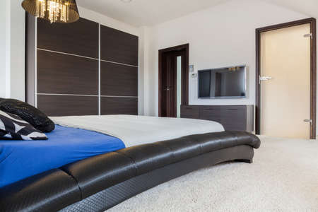 Modern bedroom with plasma TV on the wall photo