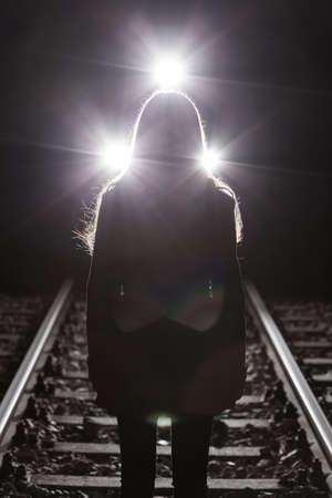 psiquico: Chica de pie en los carriles y el tren en el fondo Foto de archivo