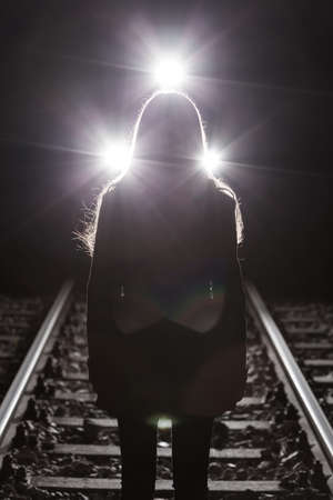 psychic: Girl standing on rails and the train in background