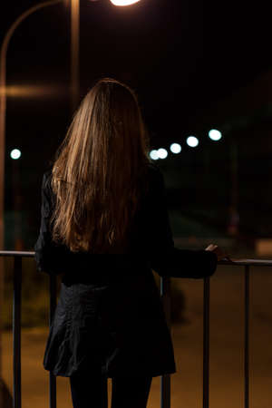 lonely road: Woman standing on a bridge wants to commit suicide Stock Photo