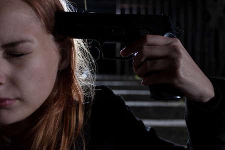 to commit: Girl with handgun going to commit suicide Stock Photo