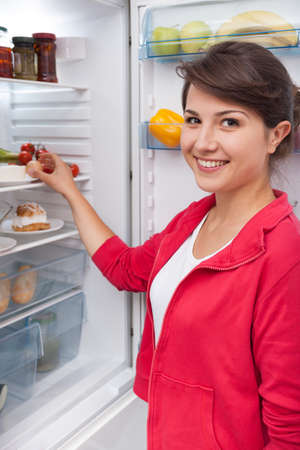 vertical fridge: Young smiling girl standing by the white fridge in the kitchen