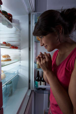 vertical fridge: Young lovely girl snacking at midnight
