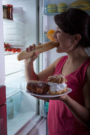 vertical fridge: Pretty young woman eating late supper