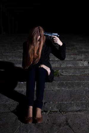 Depressed woman putting gun to her head Stock Photo
