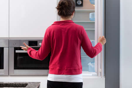 Young suprised woman and her empty  fridge