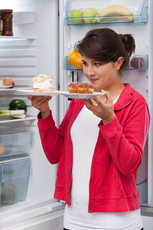 vertical fridge: Young beautiful girl and tough choice between two cakes Stock Photo