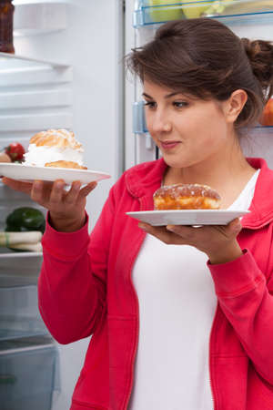 vertical fridge: Young pretty woman and two tasty pastries