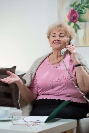 warm home: Aged happy lady and her phone conversation