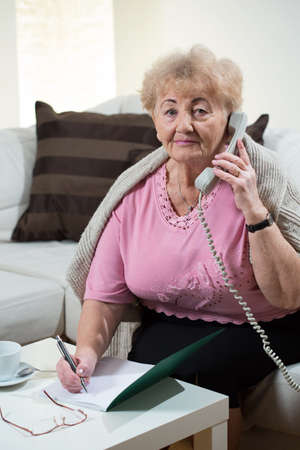 lady on phone: Elderly nice lady making notes during phone talk