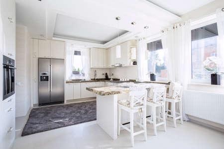 Großzügige, weiße Küche mit Theken Essplatz Standard-Bild