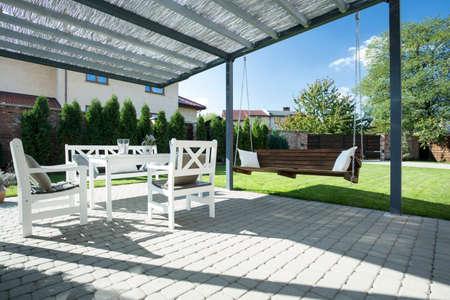 Prachtig terras met schommel in de tuin Stockfoto