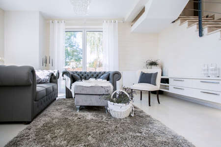view of an elegant living room: Big white living room with grey sofas