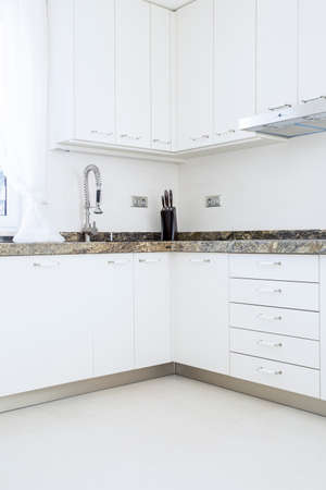 White, modern kitchen cabinets with granite top