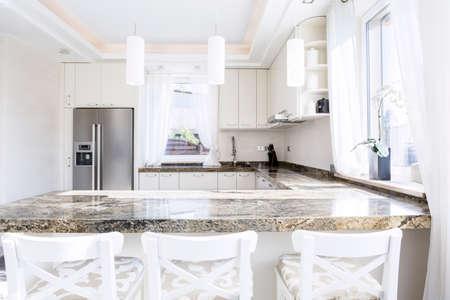 Modern, white kitchen with long granite worktop