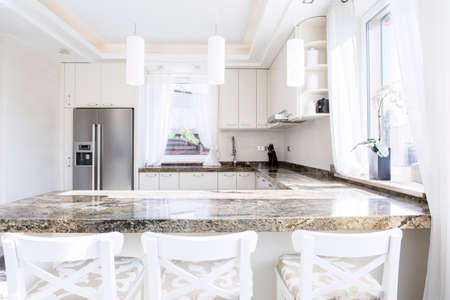contemporary kitchen: Modern, white kitchen with long granite worktop