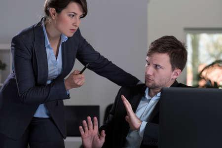 acoso laboral: Joven jefe bastante femenina amenazando a su empleado guapo joven