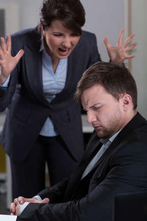 acoso laboral: Jefa joven gritando a su trabajador guapo Foto de archivo