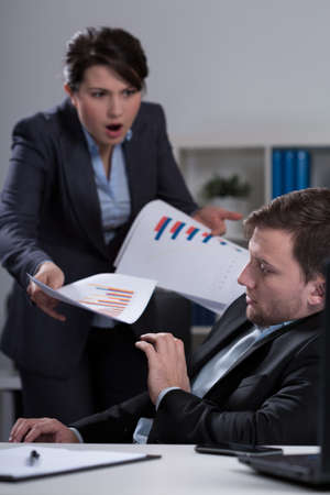 bullying: Young furious female boss and her scared young employee Stock Photo