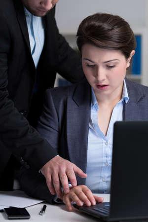 acoso laboral: Jefe atractiva joven que toca la mano de la joven