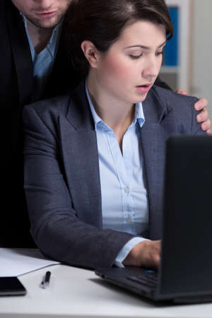 inappropriate: Young boss and his inappropriate behaviour at workplace Stock Photo