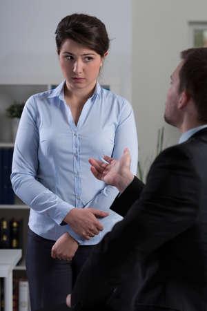 acoso laboral: Jefe joven reprender a su empleado de sexo femenino bonito joven