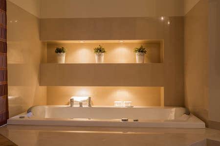 Close-up of ceramic bathtub in illuminated bathroom