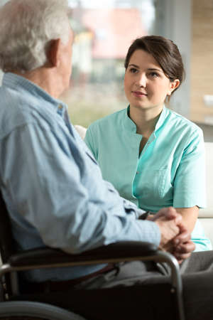 Handicapped senior man and his smiling nurse Stock Photo