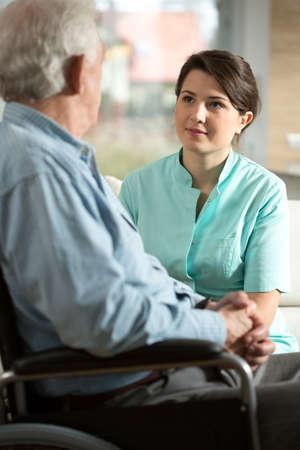pielęgniarki: Niepełnosprawnych starszy mężczyzna i jego uśmiechnięta pielęgniarka Zdjęcie Seryjne