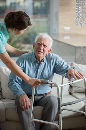 Disabled man using walking frame and helpful nurse